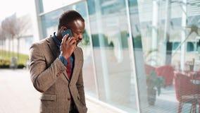 在现代办公室旁边的年轻非裔美国人的商人立场在他的智能手机谈话 他与他的事务谈话 股票录像