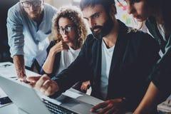 在现代办公室的工友 谈话与同事和使用膝上型计算机的有胡子的人,当坐在时 免版税库存图片