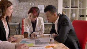 在现代办公楼,亚裔妇女的混杂的种族企业队召开会议谈和谈论项目 股票录像