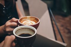在现代咖啡馆的两个人使叮当响的咖啡杯 库存图片