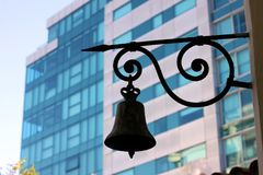 在现代大厦背景的老黑响铃  图库摄影