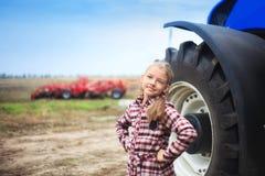 在现代拖拉机附近的逗人喜爱的女孩在领域 库存照片