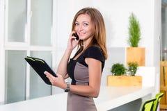 在现代明亮的办公室谈话在手机和拿着有任务名单的年轻女实业家片剂 库存照片
