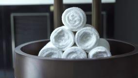 在现代温泉沙龙的堆折叠的白色滚动的毛巾在黑暗的背景 白色毛巾在黑暗的卫生间里 股票录像