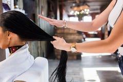 在现代温泉沙龙的护发 美发师妇女应用面具或油在头发 免版税库存图片