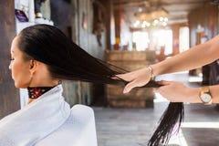 在现代温泉沙龙的护发 美发师妇女应用面具或油在客户的头发 库存图片