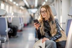 在现代火车的妇女骑马 库存照片