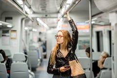 在现代火车的妇女骑马 库存图片