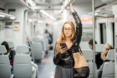 在现代火车的妇女骑马 免版税库存图片