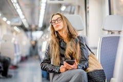 在现代火车的妇女骑马 免版税图库摄影