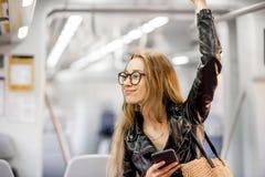 在现代火车的妇女骑马 图库摄影