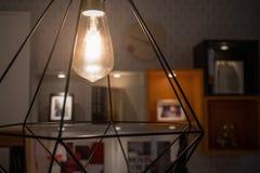 在现代灯的一个发光的电灯泡 免版税库存图片