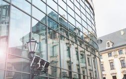 在现代玻璃大厦的老房子反射 免版税库存照片
