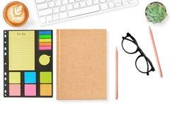 在现代白色办公桌桌上的空白的笔记本封页todo名单与大模型的供应 顶视图,平的位置 免版税库存图片