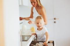 在现代白色厨房,舒适生活方式在家照顾食用与孩子女儿的早餐 免版税库存图片