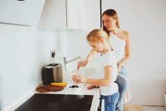 在现代白色厨房,舒适生活方式在家照顾食用与孩子女儿的早餐 库存图片