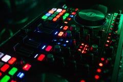 在现代管理部门的由后面照的按钮音乐的DJ的用不同的颜色 免版税库存图片