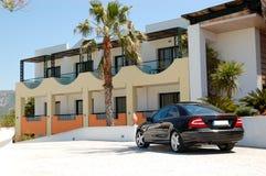 在现代豪华旅馆附近停放的汽车 免版税库存图片