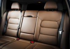 在现代豪华汽车的后面乘客座位,前面看法,红色皮革 免版税图库摄影