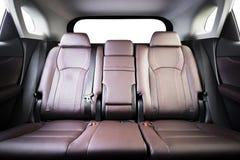 在现代豪华汽车的后面乘客座位,前面看法,红色穿孔的皮革 免版税图库摄影