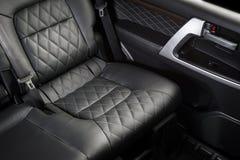 在现代豪华汽车的后面乘客座位 免版税库存图片