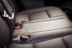在现代豪华汽车,红色穿孔的皮革的后面乘客座位 免版税库存图片