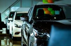 在现代陈列室里停放的新的豪华发光的小型客车 售车行办公室 汽车零售店 r 免版税库存照片