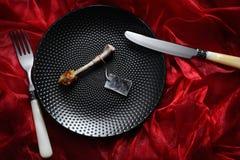 在现代黑色的顶视图桌scabbed鸡腰臀部分骨头与泡影有灰色贺卡和经典象牙的co样式板材 库存照片