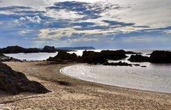 在现出轮廓岩质岛的岩石安特里姆海岸的日落在Balintoy港口附近 免版税库存照片