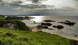在现出轮廓岩质岛, Balintoy的安特里姆海岸的日落 免版税库存照片