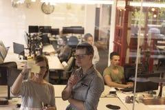 在现代办公室内部文字笔记的年轻夫妇关于贴纸 免版税图库摄影