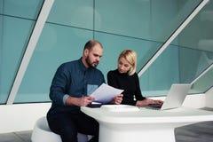 在现代办公室内部的便携式的网书的男人和妇女企业家 免版税库存照片