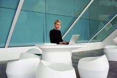 在现代办公室内部的工作天期间在便携式计算机上的典雅的女性经理键盘输入 库存图片