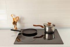 在现代厨房里打开平底深锅、平底锅和木匙子有归纳火炉的 免版税库存图片
