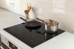 在现代厨房里打开平底深锅、平底锅和木匙子有归纳火炉的 库存图片