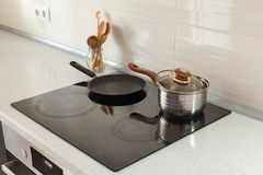 在现代厨房里打开平底深锅、平底锅和木匙子有归纳火炉的 库存照片