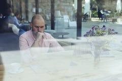 在现代咖啡店内部的商人或企业家坐的前面开放便携式计算机在城市布局 免版税库存照片