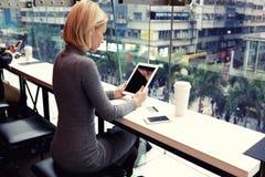 在现代咖啡店的休息期间年轻女性观看在数字式片剂的录影 免版税库存图片