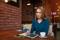 在现代咖啡店的休息期间年轻女性观看在数字式片剂的录影 免版税库存照片