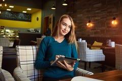 在现代咖啡店的休息期间年轻女性观看在数字式片剂的录影 免版税图库摄影