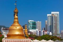 在现代城市大厦背景的金黄佛教stupa 免版税图库摄影
