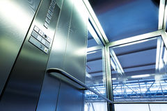 在现代大厦、发光的按钮和栏杆的里面金属和玻璃电梯 库存图片