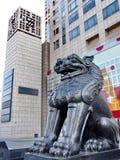在现代大厦前面的金属狮子 库存照片