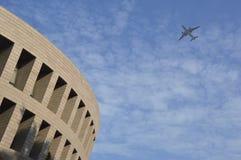 在现代大厦的飞机飞行。 库存图片