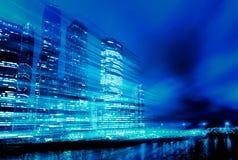 在现代大厦背景的光足迹 摩天大楼的概念夜行动迷离的 蓝色定调子 免版税图库摄影