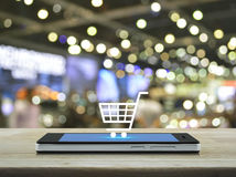 在现代巧妙的电话屏幕上的购物车象在木桌上 免版税库存图片