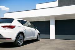 在现代房子前面的白色汽车有车库门的 库存图片