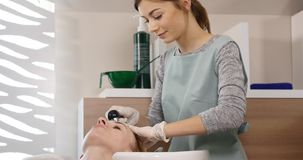 在现代温泉的护发 妇女安排头发洗由美发师在发廊 在温泉的妇女洗涤的头发 温泉 股票录像