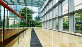 在现代玻璃办公楼的走廊 免版税库存照片