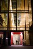 在现代玻璃大厦被点燃的大厅的入口在晚上 库存图片